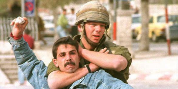 جندي اسرائيلي يمسك شاب فلسطيني، خلال مواجهات بين شبان وجنود الاحتلال في نابلس وسط البلد، 1995، تصوير أسامة السلوادي