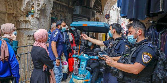 Israeli police officers enforce coronavirus regulations in Jerusalem's Old City, on July 9, 2020. (Photo by Ahmad Gharabli/AFP via Getty Images)