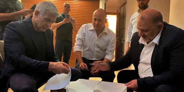 """زعيم """"القائمة العربية الموحدة"""" منصور عباس (على اليمين) يوقع على اتفاق تشكيل الحكومة مع يائير لابيد ونفتالي بينت، AFP"""