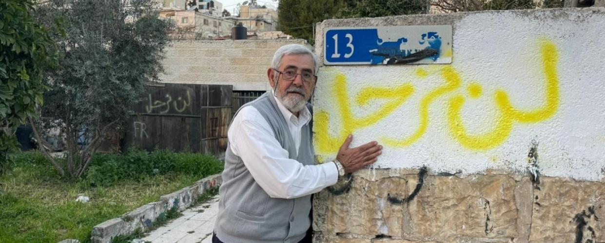"""نبيل الكرد، من سكان كرم الجاعوني منذ فترة طويلة، يقف بجانب جدار مكتوب عليه """"لن نرحل"""""""